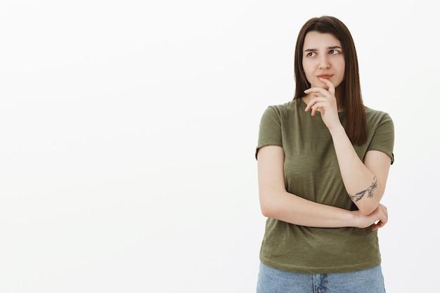 Hmm, preciso pensar sobre isso. retrato de uma colega de trabalho feminina, inteligente e criativa, focada e pensativa, com uma tatuagem fazendo um brainstorm, inventando uma ideia, olhando para o canto superior esquerdo enquanto se lembra de dados sobre a parede cinza