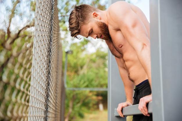 Hnadsome desportista barbudo sem camisa a fazer exercício ao ar livre
