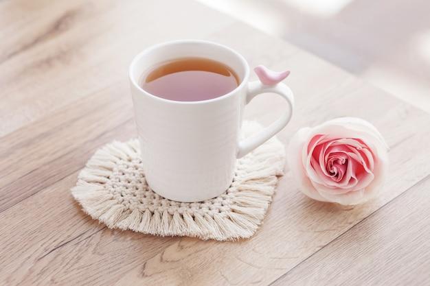 Hobby artesanal de macramé. chá em uma xícara na montanha-russa de macramê branca na mesa de madeira com a rose.