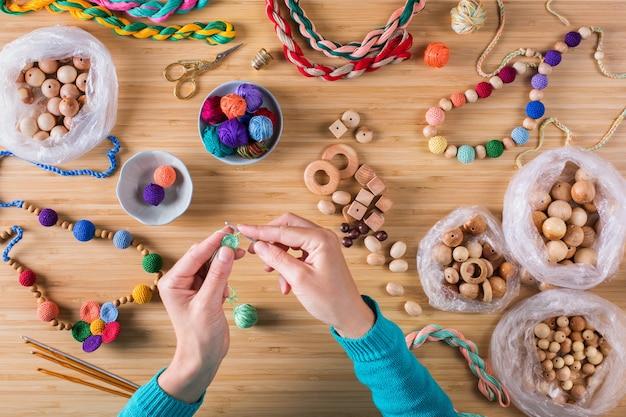 Hobby, artesanato, criatividade, conceito de tempo livre em casa. mãos femininas, tricô, crochê, fazendo algodão ecológico e miçangas coloridas de madeira para bebês, mordedores para recém-nascidos. camada plana, vista superior