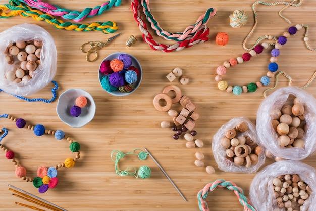 Hobby, artesanato, criatividade, conceito de tempo livre em casa. tricô, crochê, confecção de algodão ecológico e miçangas coloridas de madeira para bebês, mordedores para recém-nascidos. camada plana, vista superior