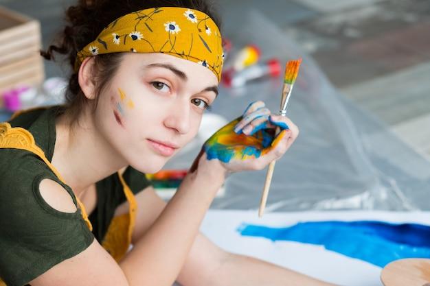 Hobby de belas artes. retrato da bela pintora feminina, deitada no chão, criando arte abstrata.