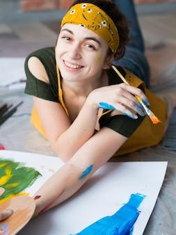 Hobby de belas artes. vista superior do pintor feminino feliz, deitado no chão, criando arte abstrata.