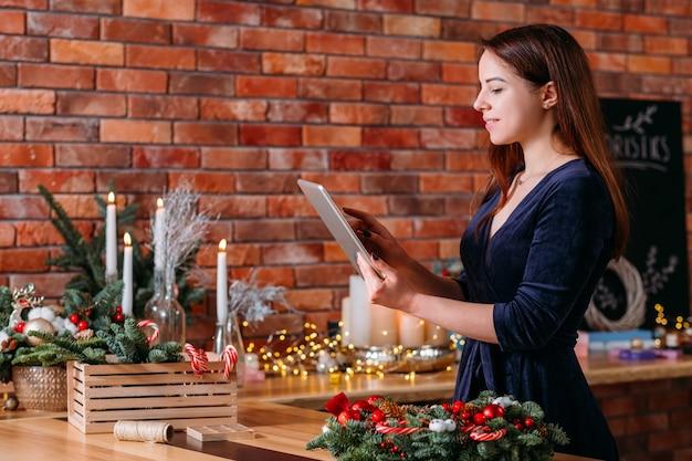 Hobby de florista. mulher gravando videoblog no tablet. espaço de trabalho de tijolos para loft