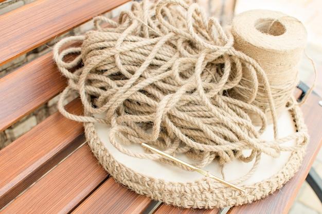 Hobby de trabalho manual tricotar uma cesta com uma corda grossa de materiais ecológicos e fundo de madeira