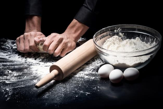 Hobby e trabalho. feche de mãos do homem assando pão enquanto amassa a massa e trabalha em um restaurante.