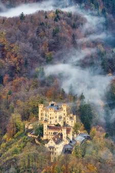 Hohenschwangau castelo bávaro amarelo antigo edifício vista aérea com uma bela neblina na floresta na temporada de outono