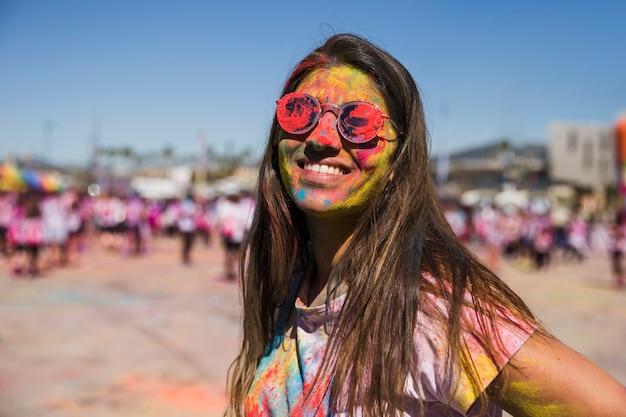 Holi cor no rosto da mulher olhando para a câmera