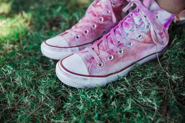 Holi cor sobre os sapatos de lona branca na grama verde
