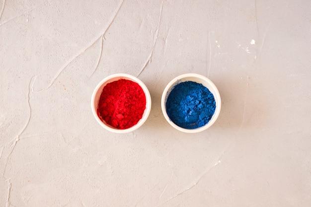 Holi pó vermelho e azul em pó na bacia branca no pano de fundo