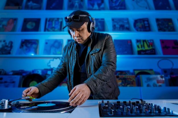 Hombre dj mezclando musica em um tornamesa com discotecas de vinil y escuchando en los audifonos
