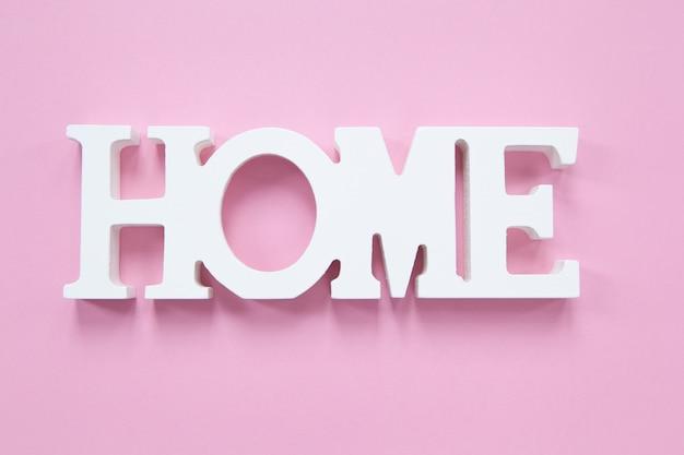 Home decorativa da palavra em um fundo cor-de-rosa millennial. conceito de conforto em casa, romance. formato horizontal.