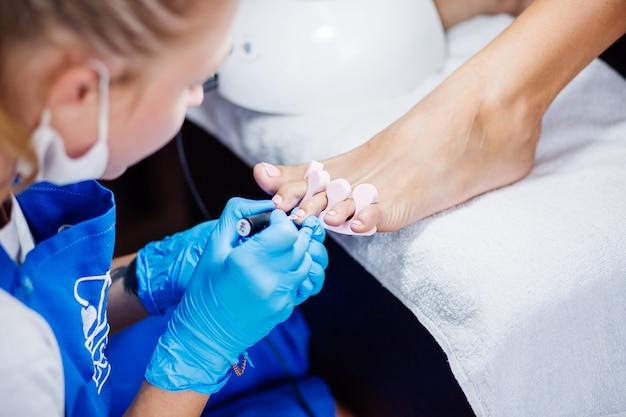 Home salon pedicure tratamento de pés e unhas o processo de pedicure profissional mestre em luvas azuis aplique esmalte de gel rosa claro