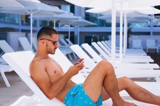 Homem à beira da piscina com telefone
