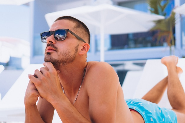 Homem à beira da piscina