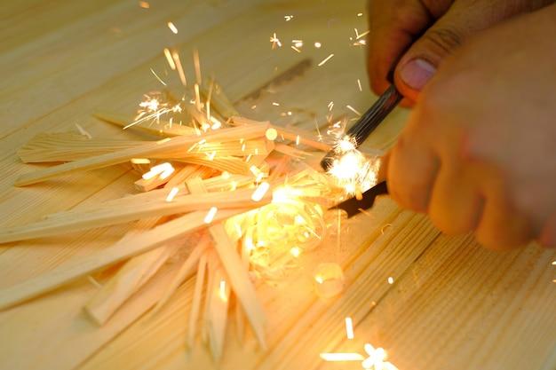 Homem, a mão inicia uma fogueira com sílex de magnésio fogo de aço