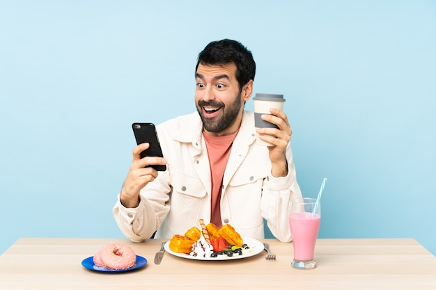 Homem à mesa tomando waffles no café da manhã e um milkshake segurando café para levar e um celular