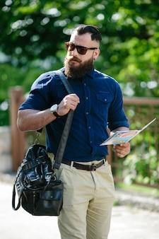 Homem à moda que anda com um mapa e uma bolsa