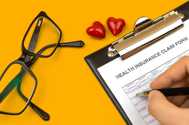 Homem a preencher o formulário de pedido de seguro saúde. área de trabalho de negócios com área de transferência, caneta e corações vermelhos em uma área de trabalho amarela. vista superior da foto