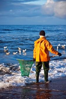 Homem à procura de âmbar no mar báltico