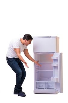 Homem à procura de comida na geladeira vazia