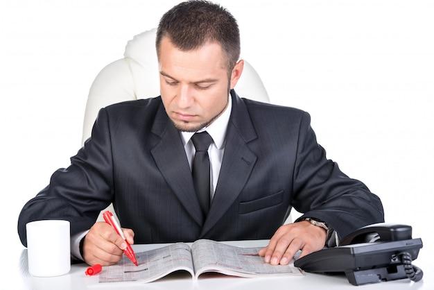 Homem à procura de vagas de emprego no jornal.