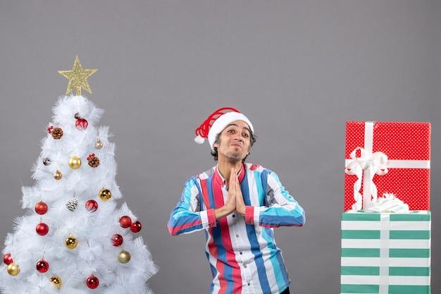 Homem abençoado de frente fazendo sinal de oração perto da árvore de natal branca