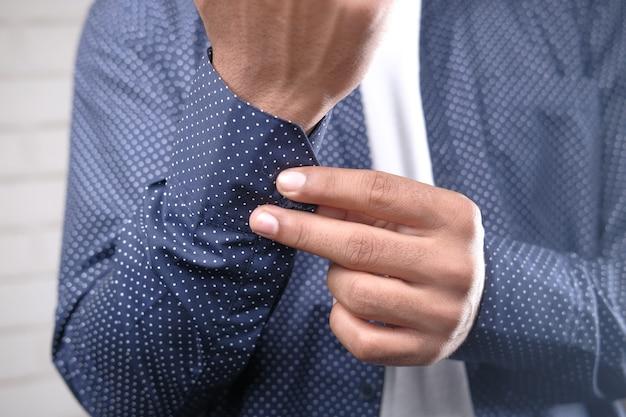 Homem abotoando a camisa de perto