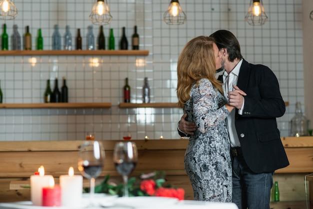 Homem abraça a mulher pela cintura em pé no salão do restaurante