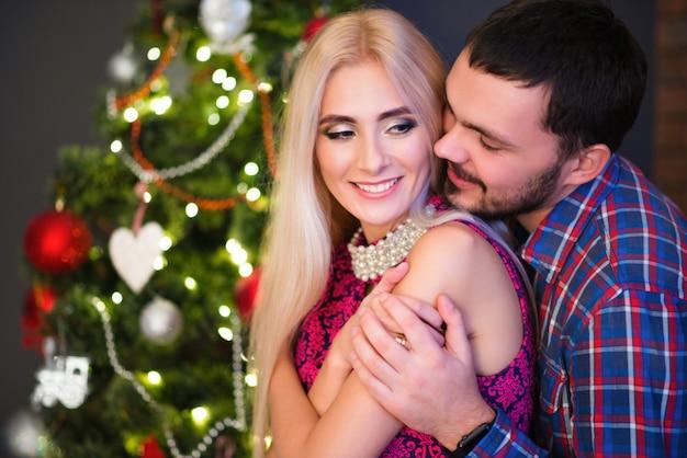 Homem abraça sua bela jovem esposa nos ombros durante os feriados de ano novo em casa