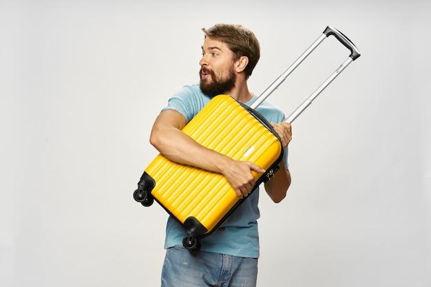 Homem abraça uma mala e desvia o olhar com interesse