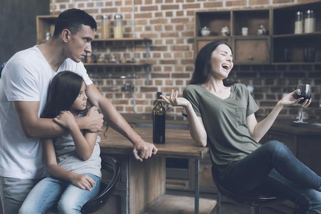 Homem abraça uma menina e olha reprovadoramente para a mulher