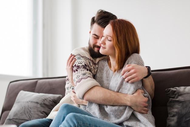 Homem abraçando a namorada na sala de estar