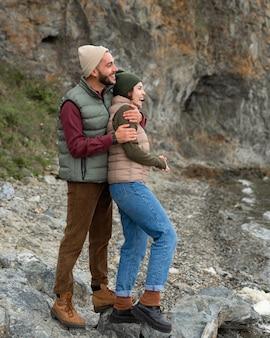Homem abraçando a namorada por trás perto do mar