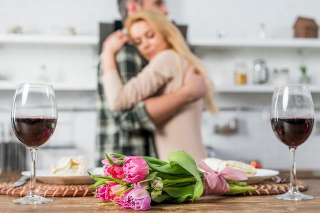 Homem, abraçando, com, mulher, perto, tabela, com, flores, e, copos vinho
