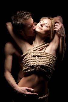 Homem abraçando e beijando sua parceira com corpo nu coberto por cordas em quarto escuro