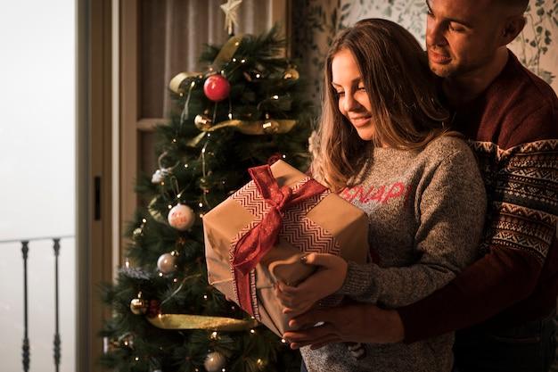 Homem abraçando mulher alegre com caixa de presente em blusas perto da árvore de natal