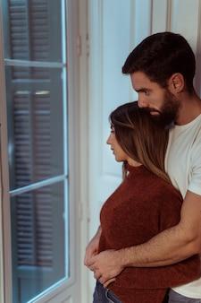 Homem, abraçando, mulher, perto, janela