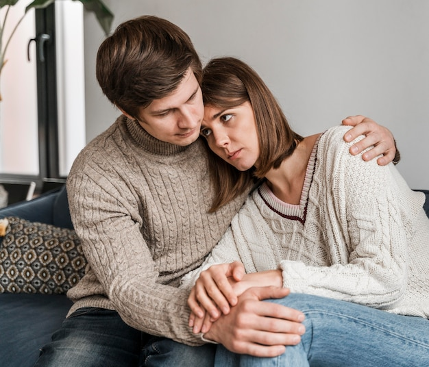 Homem abraçando mulher preocupada