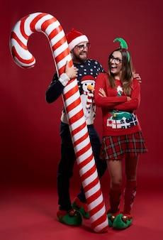 Homem abraçando o bastão de doces e sua namorada