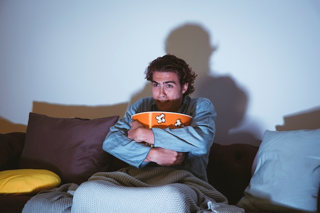 Homem abraçando pipoca assistindo um filme