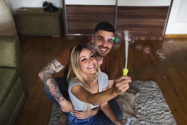 Homem abraçando sua namorada soprando bolhas em casa