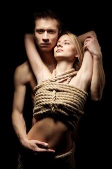 Homem abraçando sua parceira com o corpo nu coberto por cordas e olhando para a câmera em um quarto escuro