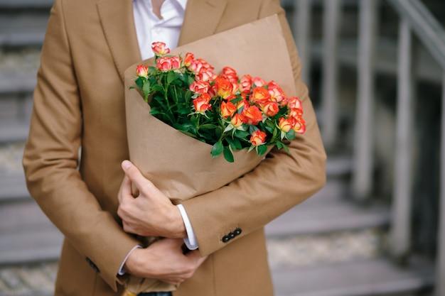Homem abraçando um buquê de flores, dobrado em papel ofício.