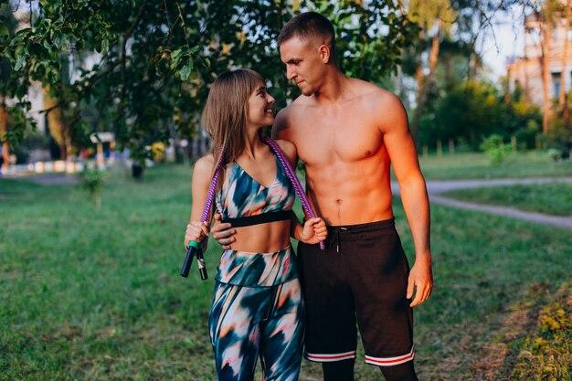 Homem abraçando uma garota. desportivo casal dançando no parque ao ar livre e olhando uns aos outros