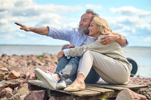 Homem abraçando uma mulher apontando a mão para a frente