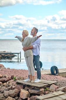 Homem abraçando uma mulher com os braços para os lados
