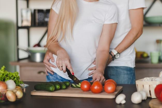 Homem, abraçar, esposa, enquanto, legumes cortando, ligado, contador cozinha