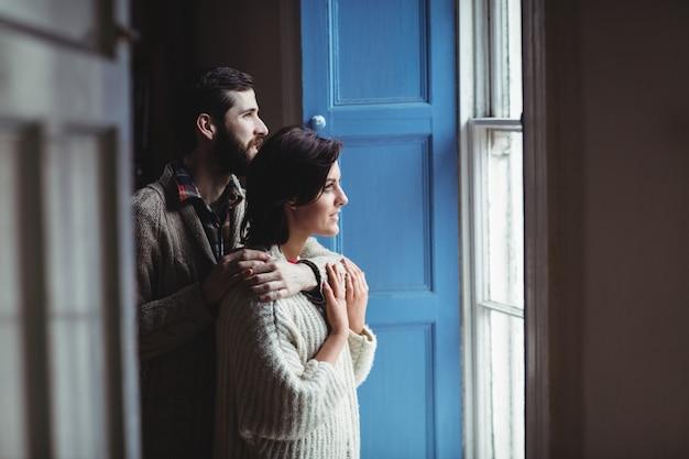 Homem, abraçar, mulher, enquanto, olhar através janela