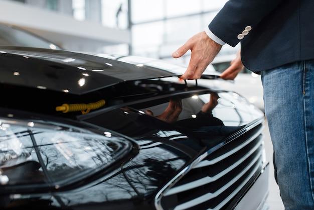 Homem abre capô de transporte na concessionária de automóveis. cliente em showroom de veículos novos, homem comprando automóvel, concessionária de automóveis